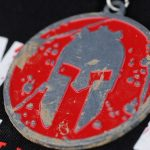 A Spartan medal on a table in Amesbury, Mass., Aug. 11, 2012. Each competitor who finished the course received a Spartan medal. (Air National Guard photo by Senior Airman Jeremy Bowcock/Released)